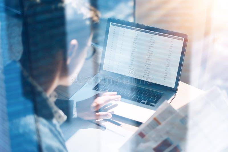 Close-upmening van de analist van bankwezenfinanciën in oogglazen die op zonnig kantoor aan laptop werken terwijl het zitten bij  royalty-vrije stock foto's