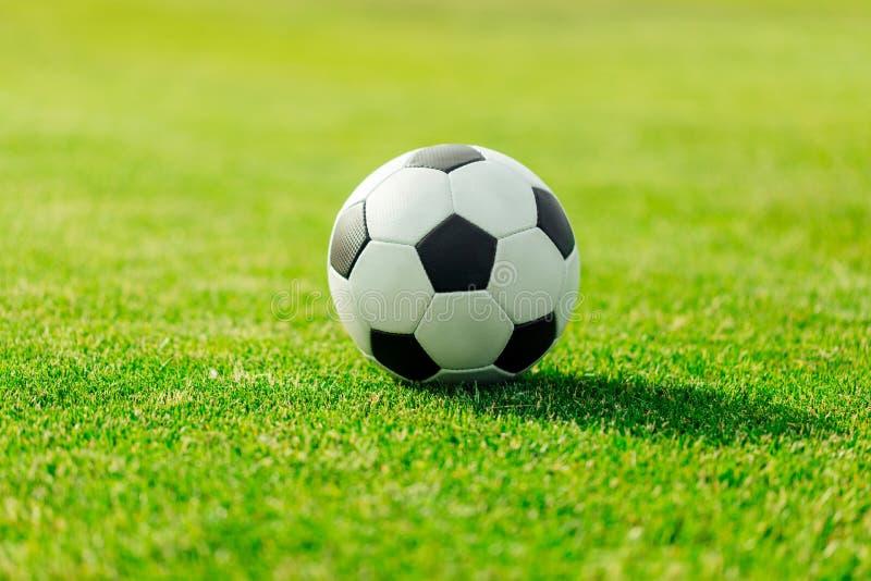 close-upmening van de bal van het leervoetbal op groen gras stock afbeeldingen
