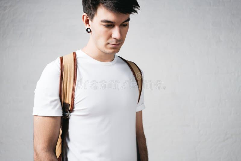 Close-upmening van de peinzende mens die witte t-shirt en rugzak dragen stock afbeeldingen