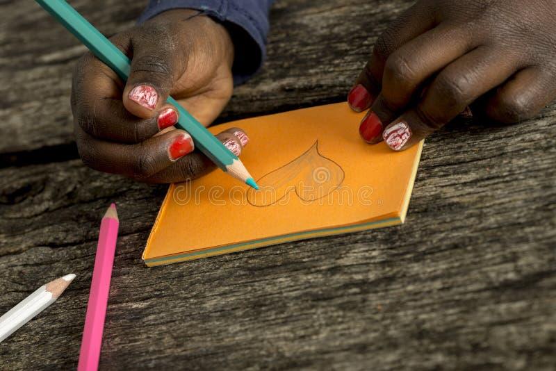 Close-upmening van een Afrikaans-Amerikaans meisje die een hartvorm kleuren stock fotografie