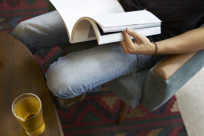 Close-upmening van een holding die van de mensenhand modern maniertijdschrift, glas lezen bier in koffie stock afbeelding