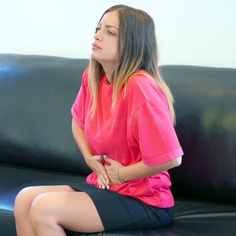Close-upmening van een jonge vrouw die pijnlijke maagpijn hebben thuis Chronische gastritis royalty-vrije stock foto