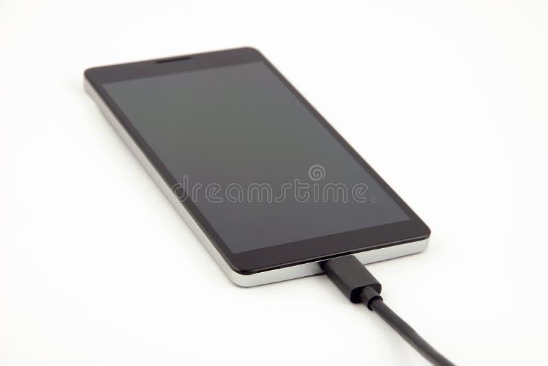 Close-upmening van een mobiele telefoon - smartphone - met zwarte het laden kabel in bijlage stock fotografie