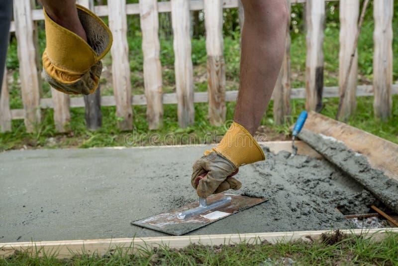 Close-upmening van een werkman die een concrete oppervlakte nivelleren royalty-vrije stock foto's