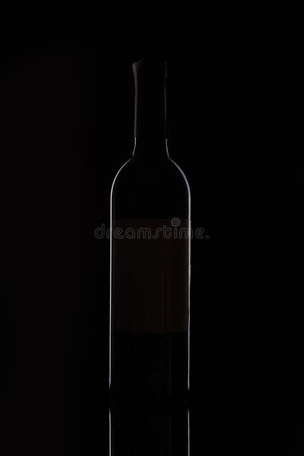 close-upmening van fles met rode die wijn op zwarte achtergrond wordt geïsoleerd stock foto