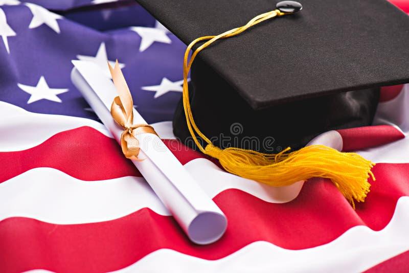 Close-upmening van graduatiebaret en diploma op de vlag van de V.S. stock foto's