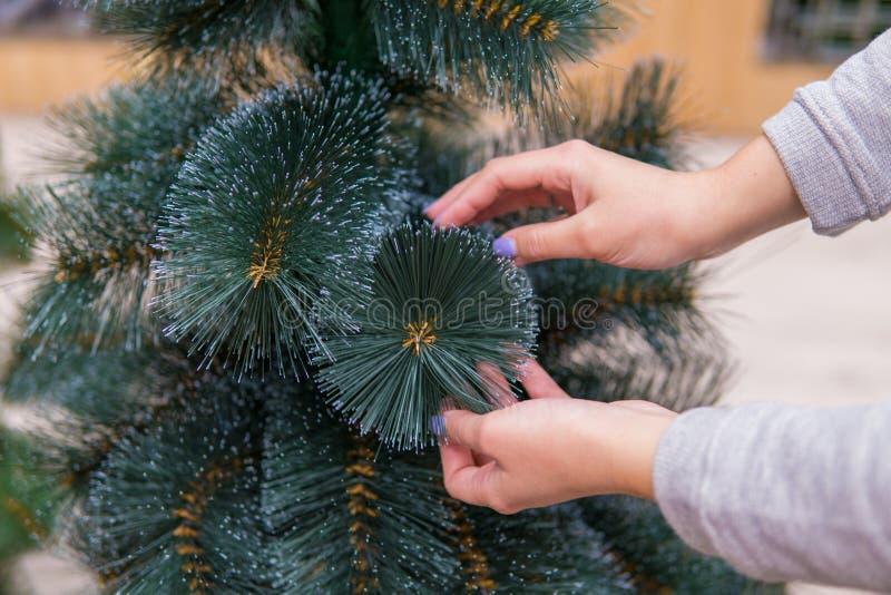 Close-upmening van handen die faux Kerstboom op Kerstavond kiezen royalty-vrije stock fotografie