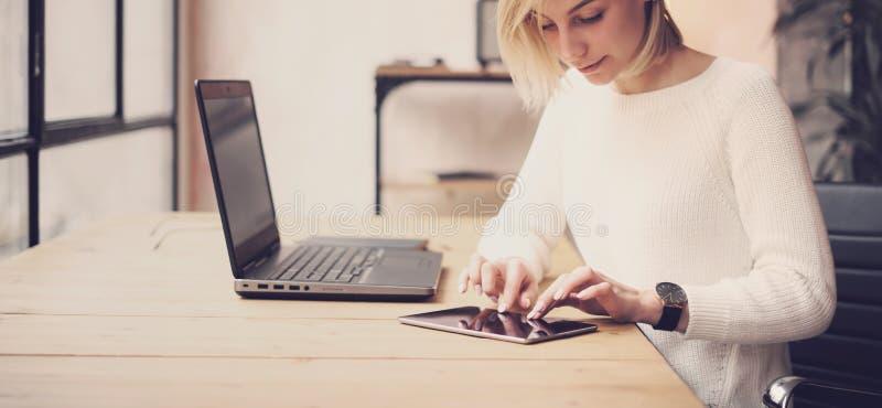 Close-upmening van het jonge mooie vrouw werken bij de houten lijst Vrouwelijke hand wat betreft tablet op werkplaats Concept stock foto