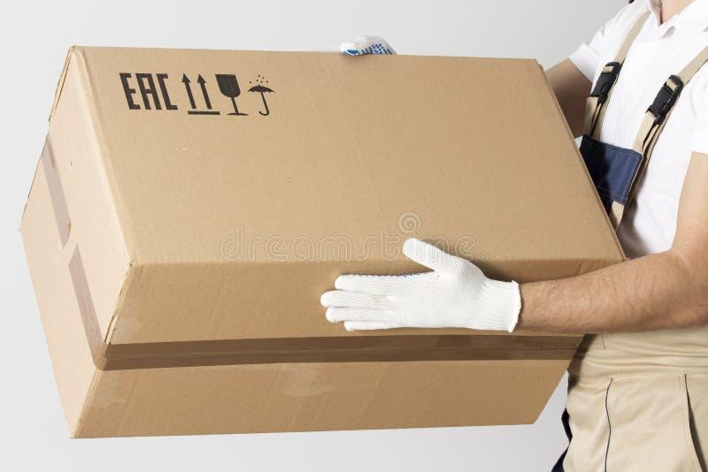 Close-upmening van kartondoos in verhuizershanden De mens van de verhuizingsdiensten in eenvormig met kartondoos stock afbeeldingen