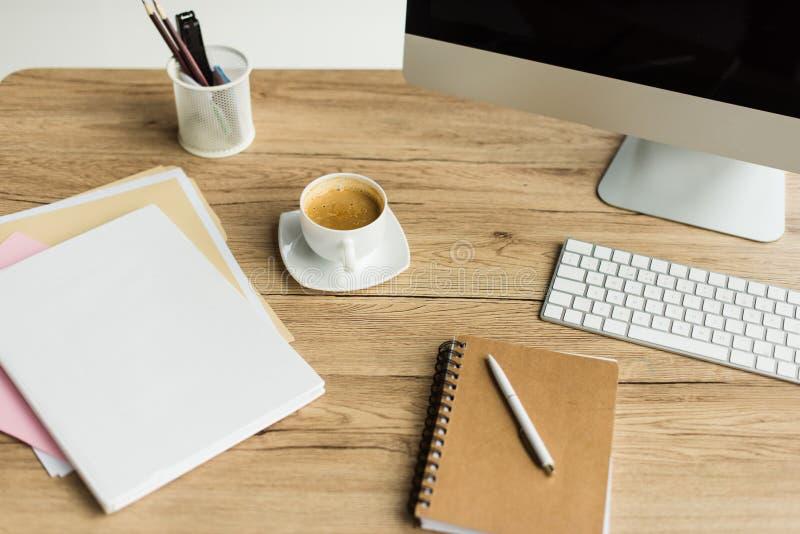 close-upmening van kop van koffie, bureaulevering en bureaucomputer stock fotografie