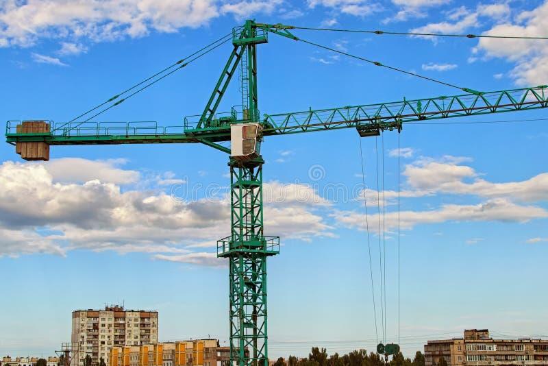 Close-upmening van kraan tegen blauwe hemel met mooie witte wolken Groene torenkraan die de nieuwe woningbouw bouwen royalty-vrije stock fotografie