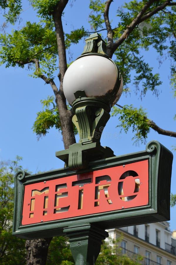Close-upmening van metro van Parijs teken door dag, boom en blauwe hemel op achtergrond stock afbeeldingen
