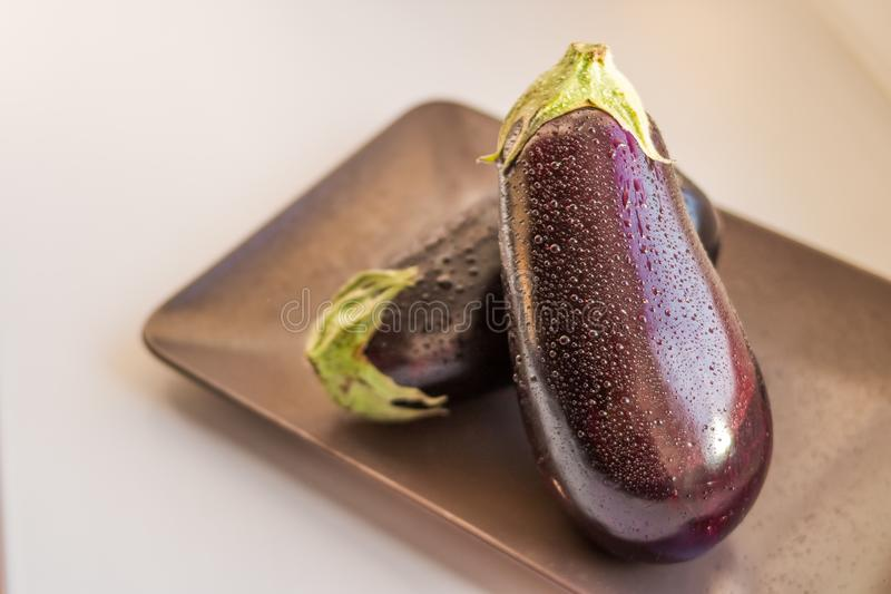 Close-upmening van natte die aubergines, auberginesfruit met dalingswater op plaat op witte achtergrond wordt geïsoleerd Ruwe aub royalty-vrije stock afbeeldingen