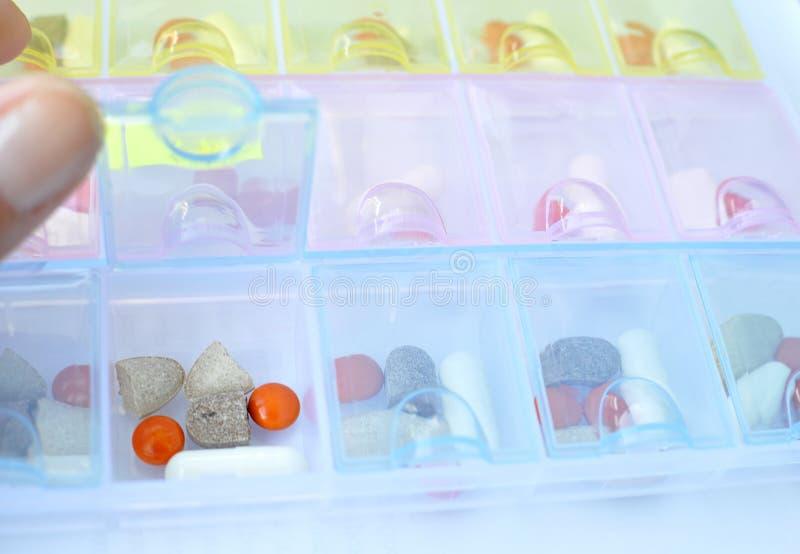 Close-upmening van open plastic pillenorganisator met drugs binnen voor een wekelijkse dosering stock fotografie