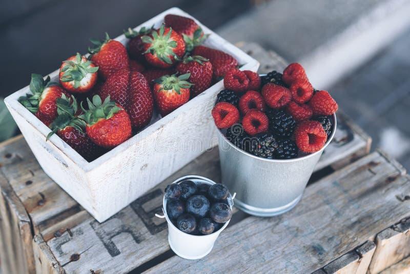 Close-upmening van sappige aardbeien, frambozen en bosbessen in een houten doos stock foto's