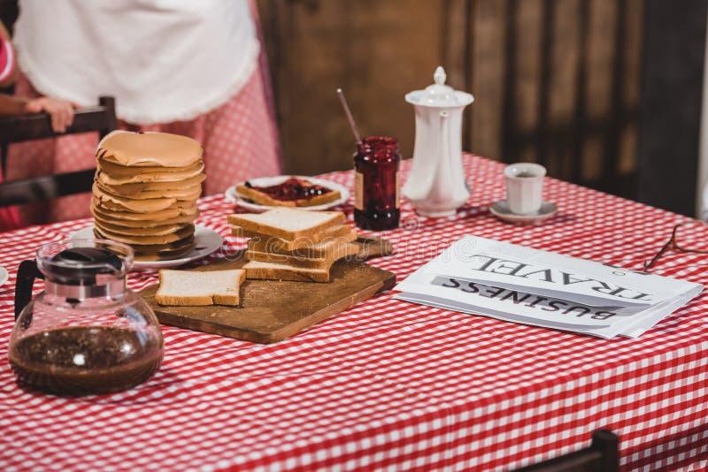 close-upmening van smakelijk ontbijt met toosts, pannekoeken, krant en koffie royalty-vrije stock afbeeldingen