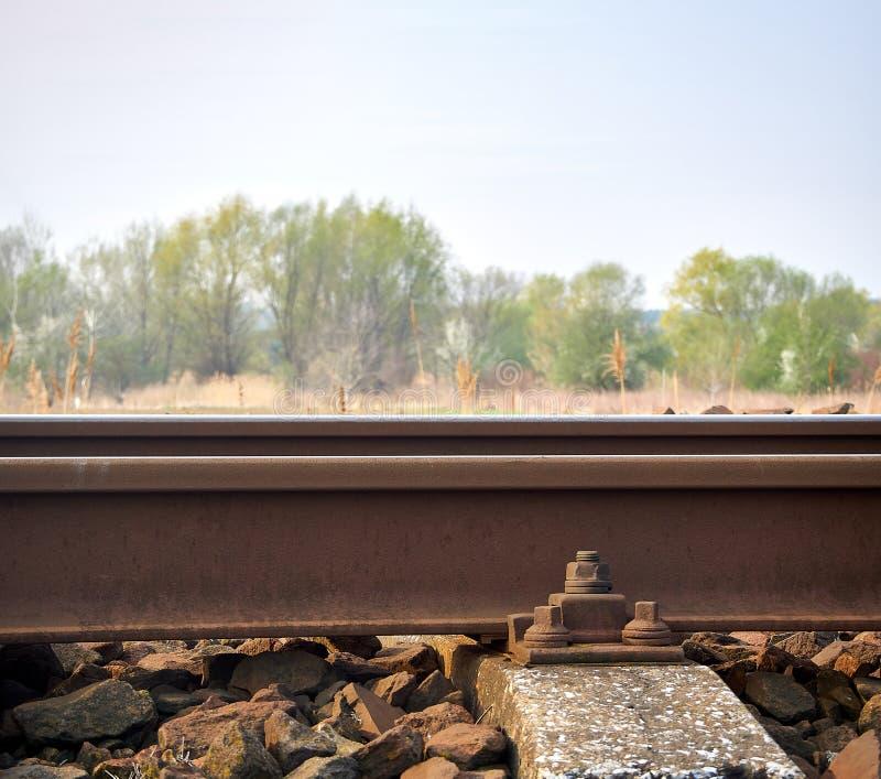 Close-upmening van sporen met concreet lijstwerk met schroef Vaag landschap op achtergrond royalty-vrije stock foto