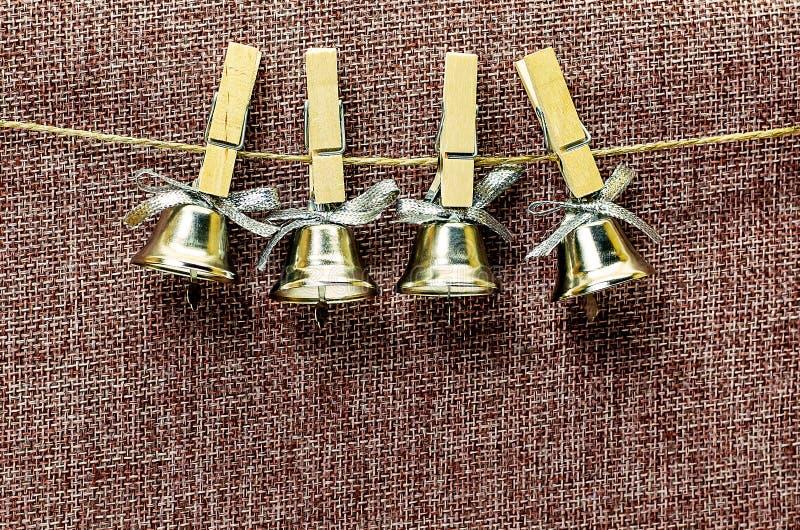 Close-upmening van vele mooie ouderwetse gouden Kerstmisklokken die als nieuw jaarspeelgoed hangen, horizontaal beeld stock fotografie