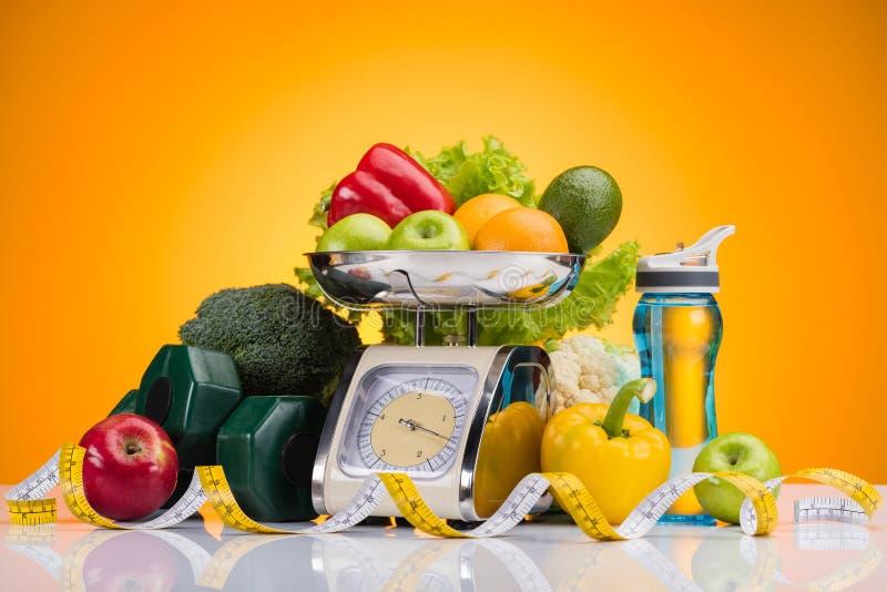 close-upmening van verse vruchten en groenten op schalen, sportenfles met water, domoren en het meten van band stock foto