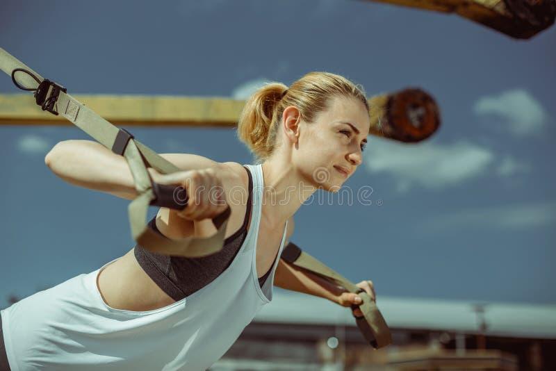 Close-upmening van vrolijke vrouw die duwups stedelijke training voor wapens doen royalty-vrije stock foto's