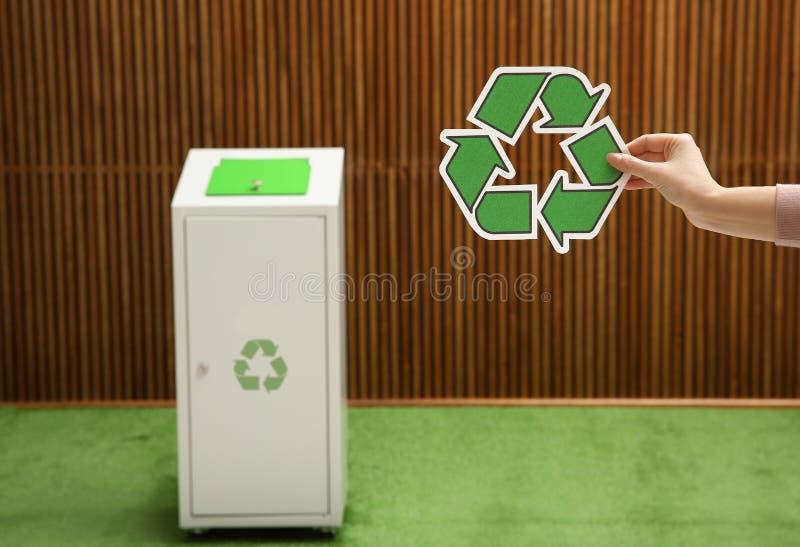 Close-upmening van vrouw met het recycling van symbool en vage afvalbak op achtergrond stock afbeelding
