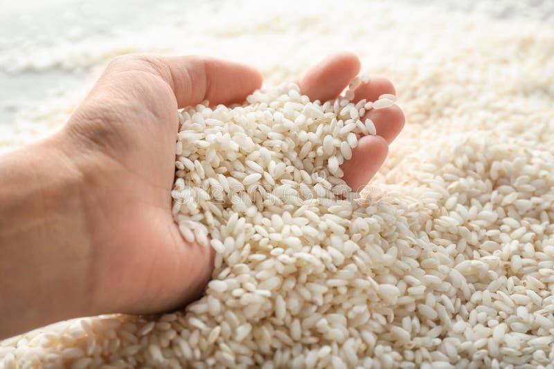 Close-upmening van vrouwelijke hand met rijst royalty-vrije stock foto