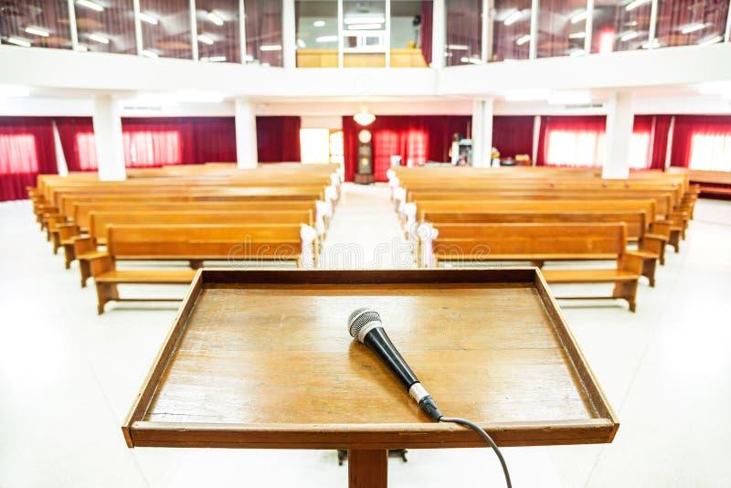 Close-upmicrofoon in lege kerk met lege banken stock fotografie