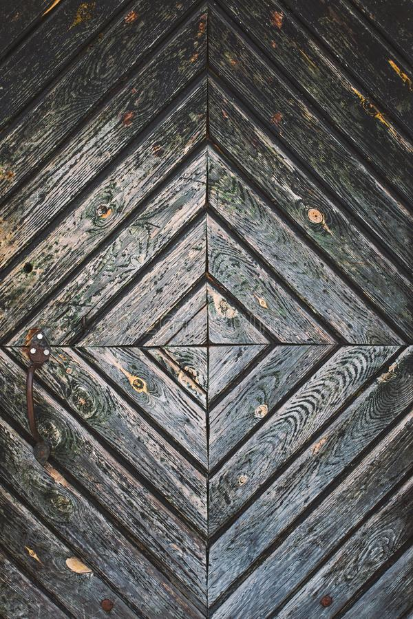 Close-upoppervlakte van oude uitstekende houten deur met roestig handvat stock afbeeldingen