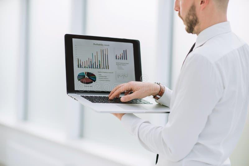 close upp affärsman som analyserar finansiella data på bärbara datorn arkivfoto