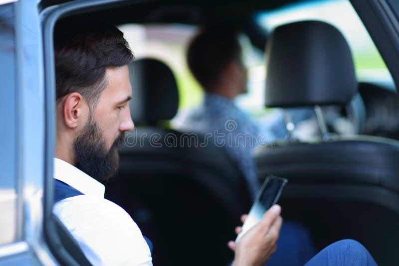 close upp affärsman som använder smartphonen, medan sitta i bil fotografering för bildbyråer