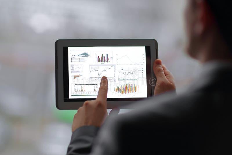 close upp affärsmannen analyserar den finansiella rapporten genom att använda den digitala minnestavlan royaltyfri foto