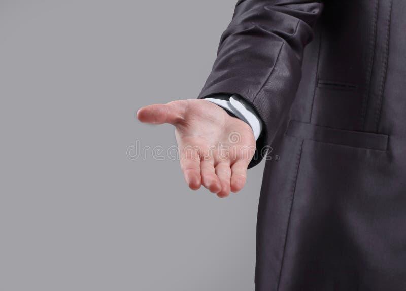 close upp affärsmannen når ut till partnern på grå bakgrund arkivbild