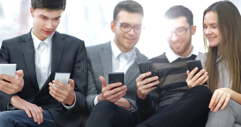 close upp aff?rslaget anv?nder deras smartphones royaltyfri bild