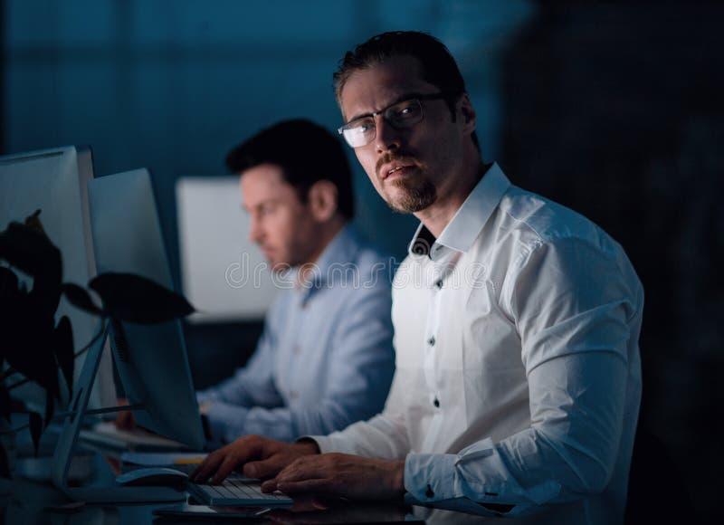 close upp allvarlig affärsman som arbetar på natten fotografering för bildbyråer