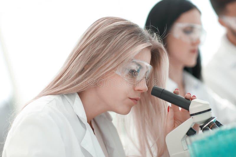 close upp allvarlig kvinnlig forskare som ser in i mikroskopet i labb arkivbild