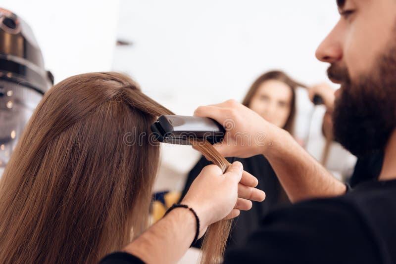 close upp Den kvinnliga frisören rätar ut brunt hår till kvinnan som använder hårjärn i skönhetsalong arkivbild