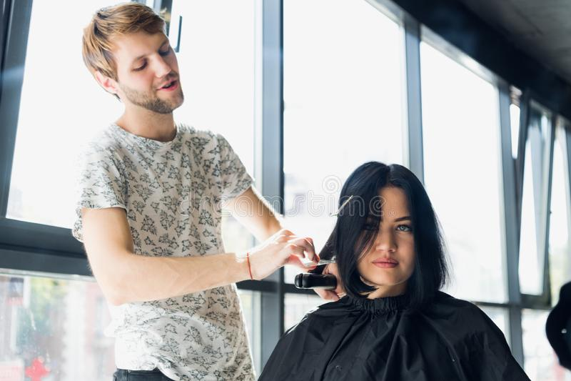 close upp Den kvinnliga frisören rätar ut brunt hår till kvinnan som använder hårjärn i skönhetsalong Den kvinnliga stylisten gör royaltyfri bild