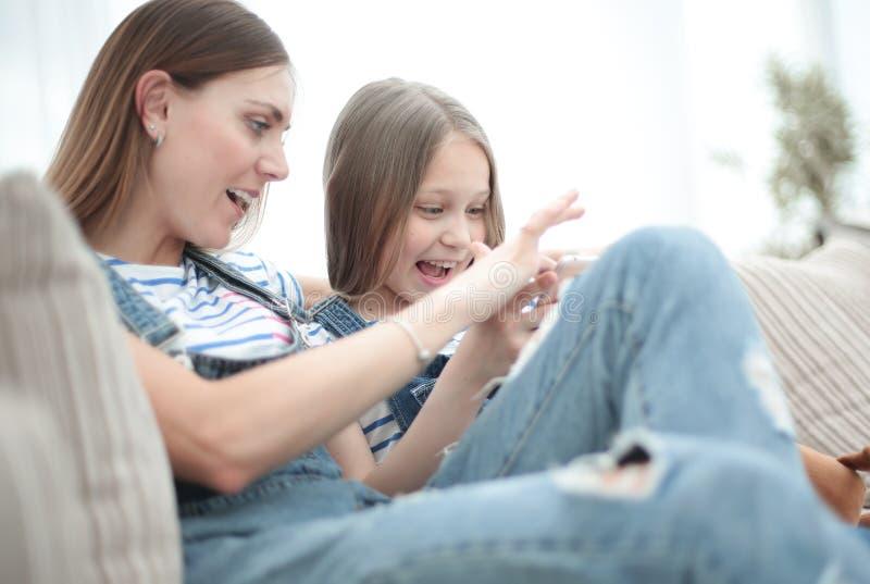 close upp den lyckliga mamman och hennes dotter håller ögonen på video på smartphonen royaltyfria foton