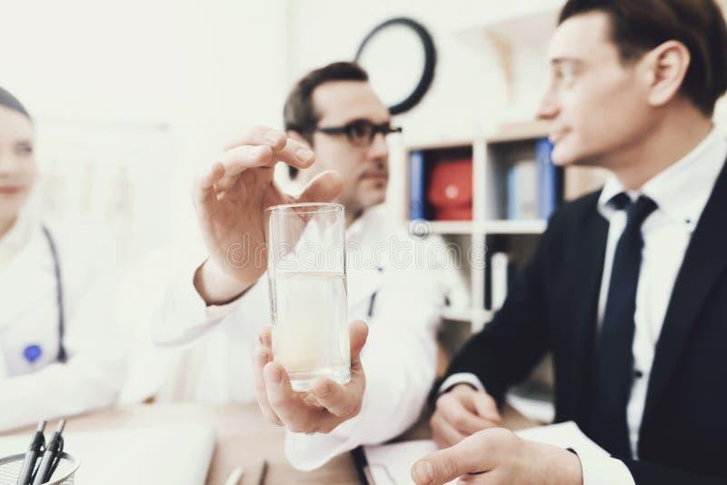 close upp Doktorn kastar huvudvärkstabletten in i exponeringsglas av vatten Behandling av huvudvärken arkivfoto
