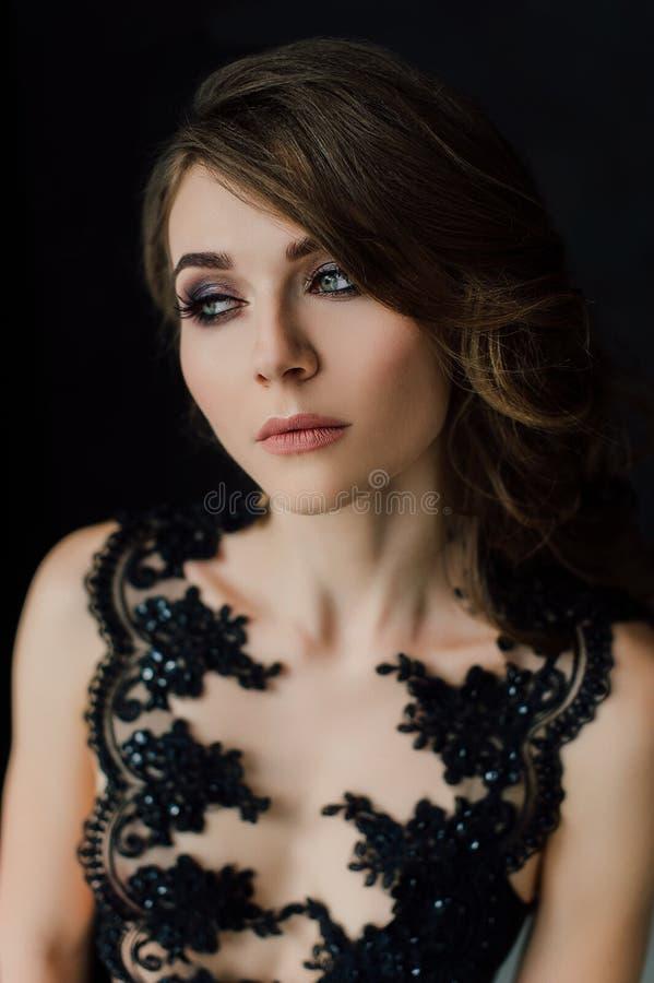 close upp egenart Fundersam elegant dam i svart studentbalaftonklänning Studio retuscherat foto royaltyfria bilder