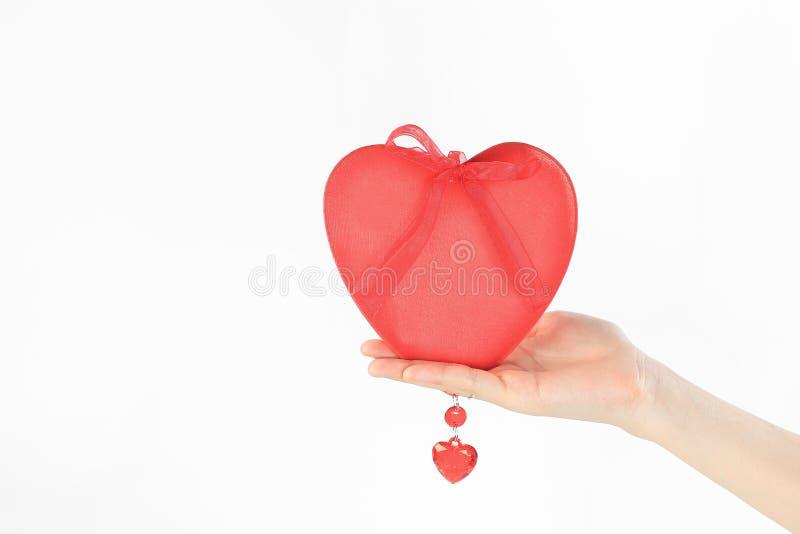 close upp en röd hjärta i en hand för kvinna` s bakgrund isolerad white royaltyfri foto