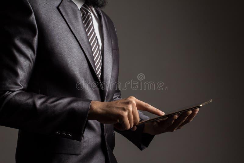 close upp Hand av affärsmannen i grå dräktinnehav och trycka påapplikation som kontrollerar tillväxttakten av aktiemarknaden royaltyfri fotografi