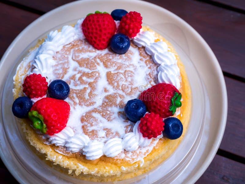 close upp Krämig mascarponeostkaka med jordgubbe- och vinterbär Japansk ostkaka close upp Julefterrätt royaltyfri bild