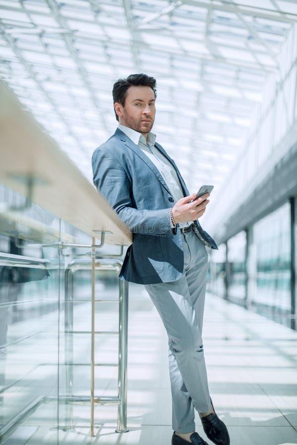 close upp läsande SMS för affärsman anseende i flygplatsbyggnaden arkivfoto