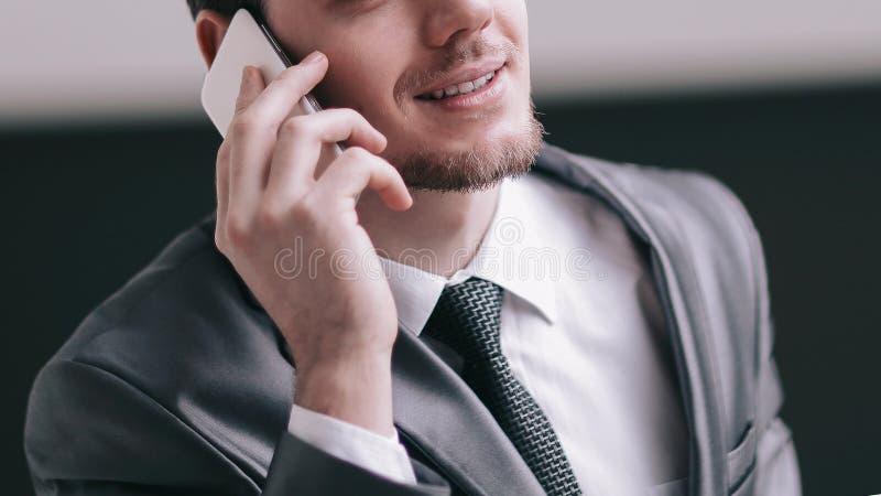 close upp le affärsmannen som i regeringsställning talar på smartphonen royaltyfri foto