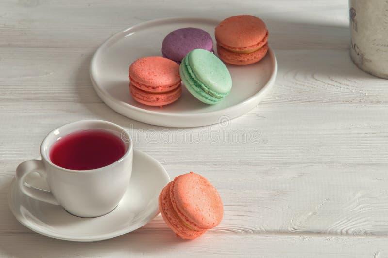 close upp Ljusa pastellfärgade macarons för fransk frukost på en rund platta, en kopp av bärte vitt trä för bakgrund kopiera avst arkivfoton