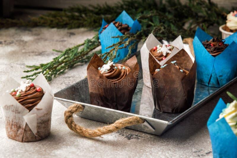 close upp Ljusbruna muffin för söt choklad Överkant som dekoreras med en kräm- hatt med julsnöflingor av mastix Grå färgbakgrund royaltyfria foton