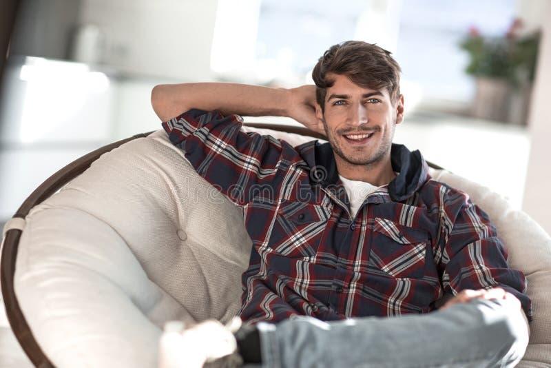 close upp lyckad ung man som sitter i en stol arkivbilder