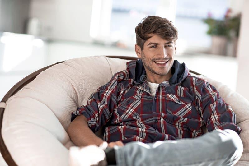 close upp lyckad ung man som sitter i en stol royaltyfri fotografi