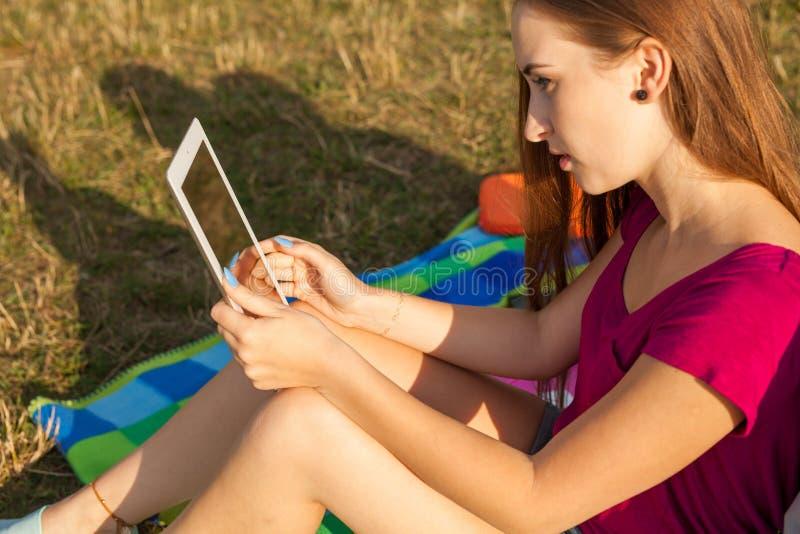 close upp Parkerar den hållande minnestavlaPC:n för ung lycklig flicka in royaltyfri foto